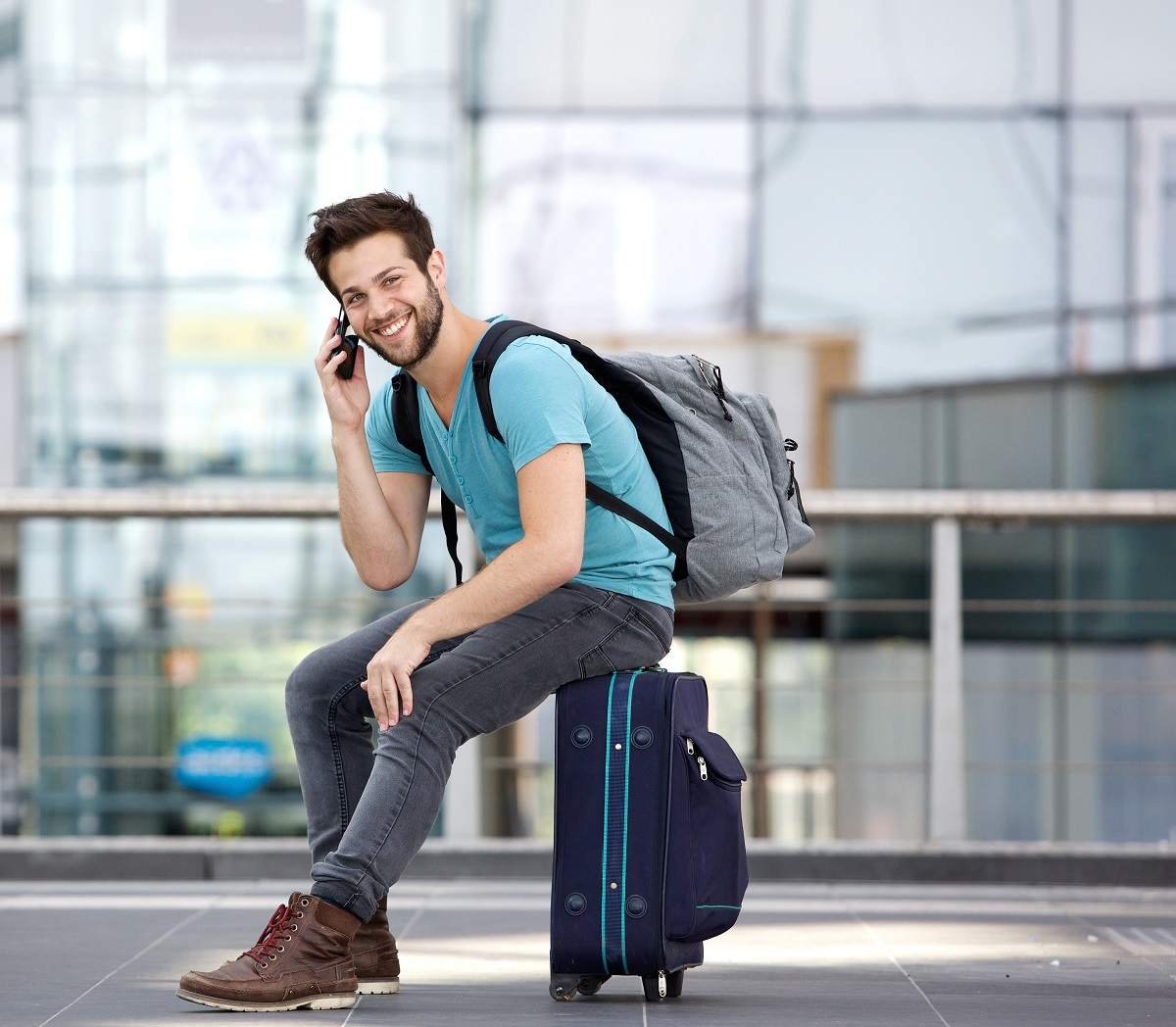 Young man sitting on his suitcase in the airport