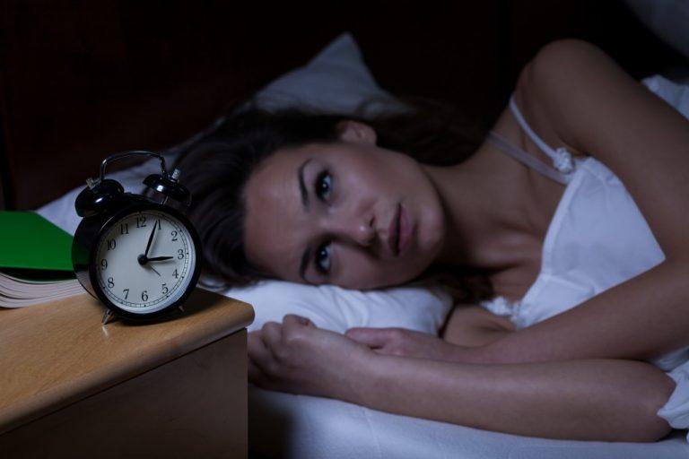 woman staring at her alarm clock