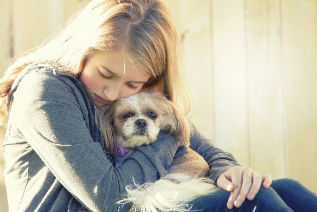 Sad female hugging dog