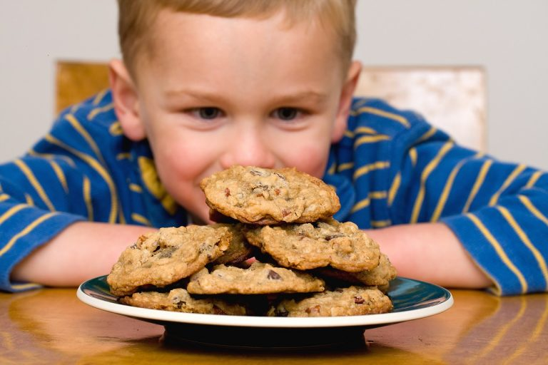 kid looking at a plate of cookies